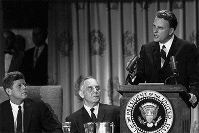 Billy Graham preached at the 1963 National Prayer Breakfast as John F. Kennedy listened attentively.
